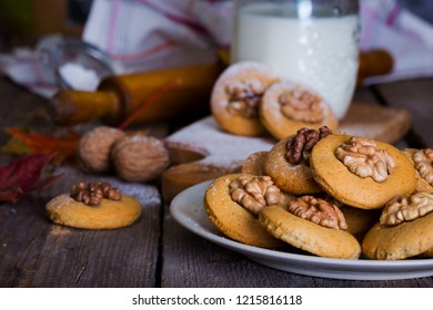 gingerbread cookies with walnuts on a table and a cup of milk