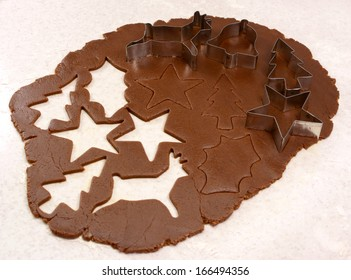 Gingerbread dough rolled out with cutout shapes and cookie cutters - star, reindeer, Christmas tree, holly leaf and bell