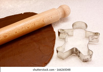 Gingerbread dough, wooden rolling pin and gingerbread man cookie cutter