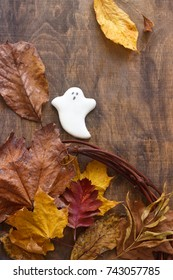 Gingerbread ghost for halloween, decorated with autumn leaves, on a wooden background. Selective focus.