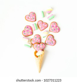 Gingerbread heart cookies and marshmallow in waffle cone on white background. Flat lay. top view.