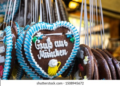 """Gingerbread heart in munich typical tourist souvenir from bavaria city and oktoberfest. Text is reading """"greetings from munich"""". Woman love this as a gift dressed in traditional dirndl clothing"""