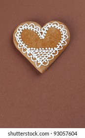 Gingerbread heart on brown background