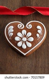 Gingerbread heart and red ribbon on brown wooden background. Shallow dof