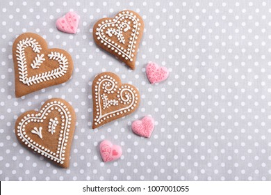 Gingerbread hearts decorated with icing on a gray background.