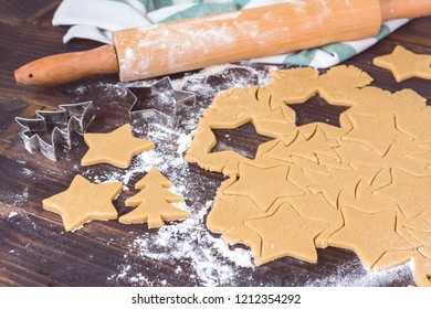 Gingerbread homemade cookies preparation for Christmas fest. Wooden table flat lay composition with rolling pin.