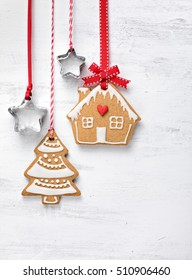 Gingerbread House and Christmas Tree cookies with red ribbon hanging over a white painted background.
