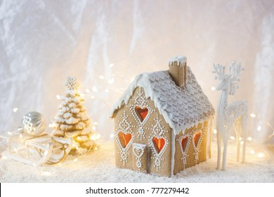 Gingerbread house, Christmas trees and a figure of a deer on a luminous background. Bokeh effect, selective focus.