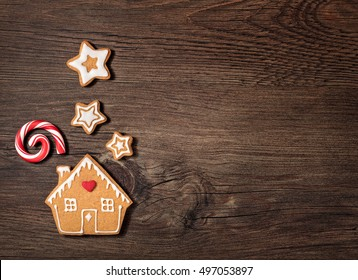 Gingerbread House cookie with candy cane chimney smoke and stars or snow over a wooden background.