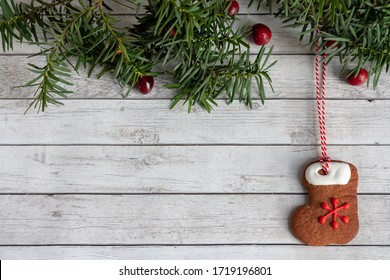 Gingerbread house decorated with royal icing on a wooden background with green branches and red berries and space for text