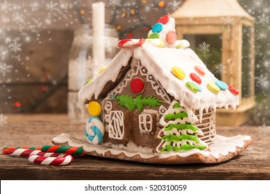 Gingerbread house. European Christmas holiday traditions. Christmas gingerbread house, lantern and candle on old wooden table. Christmas holiday sweets