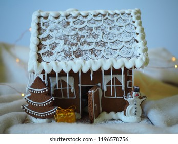 Gingerbread house with glaze, christmas tree, gift and snowman, homemade