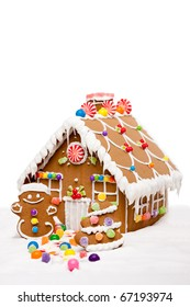 Gingerbread house, man and Christmas tree covered with snow and colorful candy on a winter landscape, isolated.
