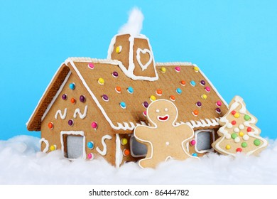 Gingerbread house with gingerbread man and christmas tree.