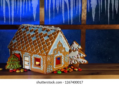 Gingerbread house on the background of the night window. Christmas gingerbread house. Night sky outside the window.