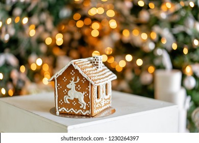 Gingerbread house on table. Defocused lights of Christmas tree. Morning in the bright living room. Holiday mood. Figure deer