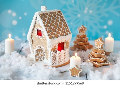 Gingerbread house and gingerbread trees on a festive Christmas background with snowflakes. Christmas postcard