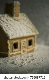Gingerbread house in winter lights covered with icing sugar and snowflakes. Shallow focus
