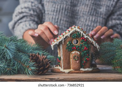 gingerbread house and women's hands, the concept of preparation for the Christmas holidays