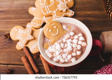 Gingerbread man bathes in a cup of hot chocolate or cocoa with marshmallow.