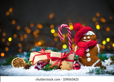 Gingerbread man with Christmas presents in snow