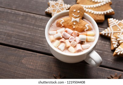 Gingerbread man in cup of hot cocoa and cookies on dark wooden table with copy space