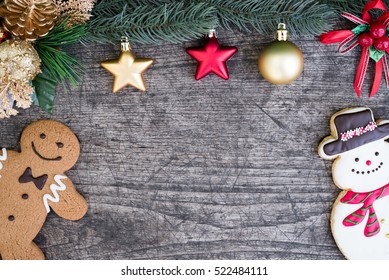 Gingerbread man with snowman cookie and fir tree decoration with red and gold ornaments on wooden table background with copy space for text, Greeting card style for merry xmas and happy new year