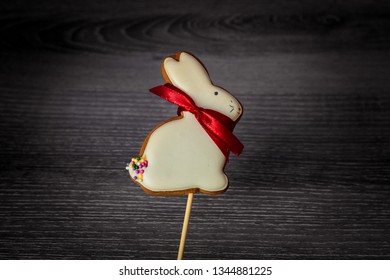 gingerbread on a stick in the form of a white Easter bunny with a red bow on a wooden surface