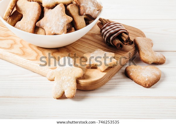 Gingerbread in the plate,cinnamon,wooden breadboard.Cooking concept.White wooden table.Close-up view