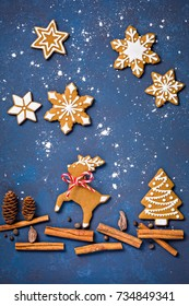 Gingerbread reindeer Christmas Cookie scene with spices over blue background.