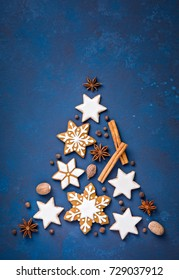 Gingerbread Snowflakes and cinnamon star cookies with spices in the shape of a christmas tree, over a blue background.