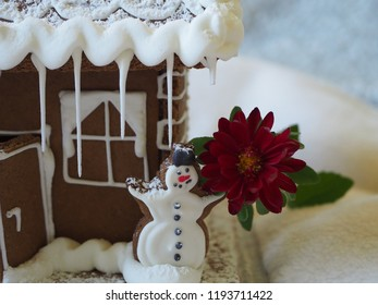 Gingerbread snowman with red flower in front of a gingerbread house