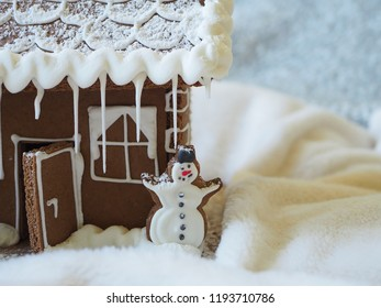 Gingerbread snowman with white icing in front of a gingerbread house