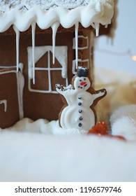 Gingerbread snowman with white icing in front of a gingerbread house with lights