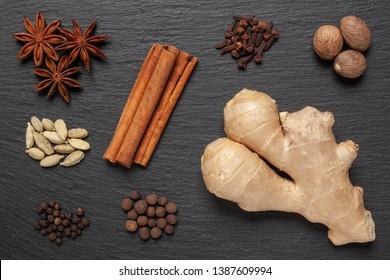 Gingerbread spices on slate - star anise, cinnamon, cloves, nutmeg, ginger, cardamom, black pepper, allspice