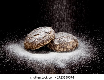 gingerbread sprinkled with powdered sugar on a black background