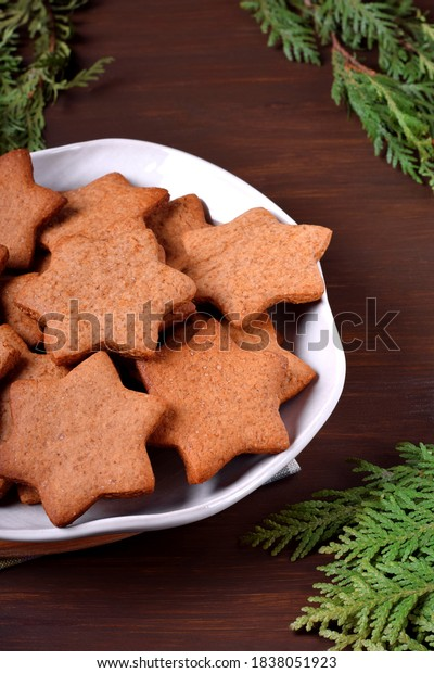 Gingerbread star cookies on the ceramic plate on the wooden table. Christmas pastry