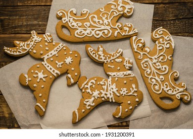 Gingerbreads painted with white glaze in the form of deer and sleigh on parchment paper on a wooden table. New Year's sweets, Christmas sweets, top view.