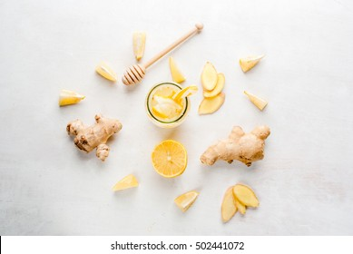Ginger-lemon drink in a bottle with a straw. Selection of the ingredients of ginger cocktail or tea: ginger root, lemon, honey. On white table. Top View,copy space
