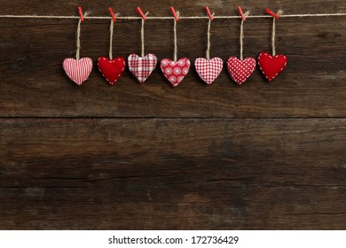 Gingham Love Valentine's hearts natural cord and red clips hanging on rustic driftwood texture background, copy space