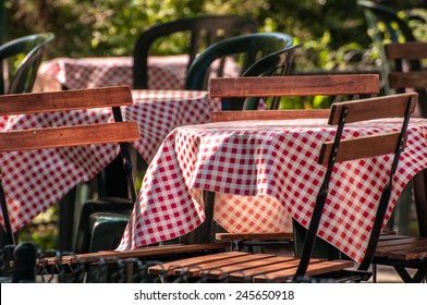 Gingham table cloths cover tables at an outdoor cafe in a garden in Paris France.