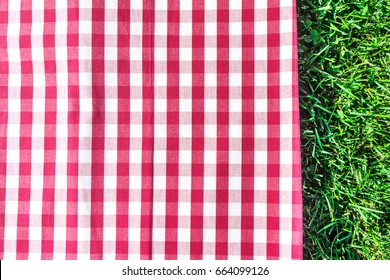 A gingham tablecloth on green grass, a template for picnic-related design, overhead shot
