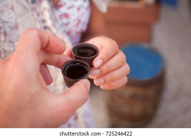 Ginja de Obidos, traditional cherry liquor of Portugal,  in the hands of tourists, close-up