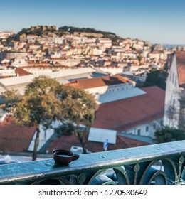Ginja de Obidos, traditional sour cherry liquor, served in small cups made of chocolate with Lisbon panorama background
