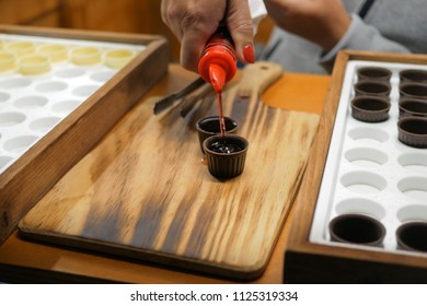 Ginja / Ginjinha cherry liqueur drink being poured into chocolate cups on Wooden background.  Traditional Portuguese drink common in many areas of Portugal especially Lisbon and Obidos.