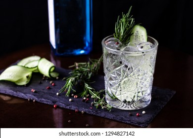 Gin-tonic alcoholic cocktail. Cucumber, rosemary, ice. On a black wooden background.