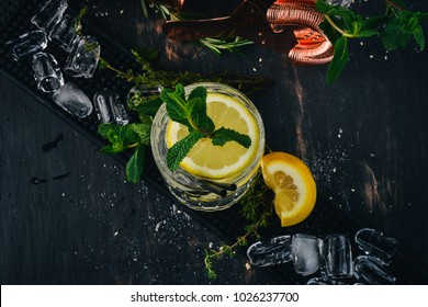 Gin-tonic alcoholic cocktail. Orange, liquor, ice. On a black wooden background.