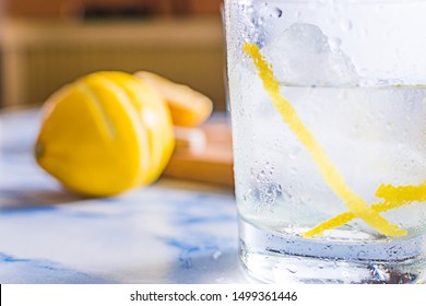 Gintonic cocktail in a glass with ice and lemon, with the ingredients aside.
