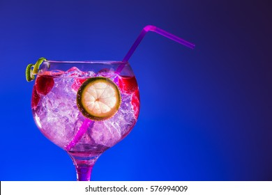 Gintonic rose with raspberries, on blue background