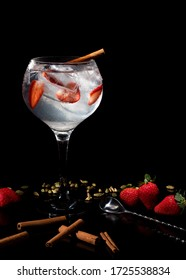 Gintonic with strawberries slice and cinnamon isolated on black background